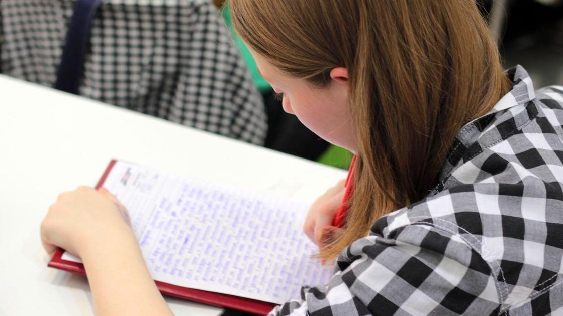 Девушка сидит за партой и пишет ручкой на листке бумаги