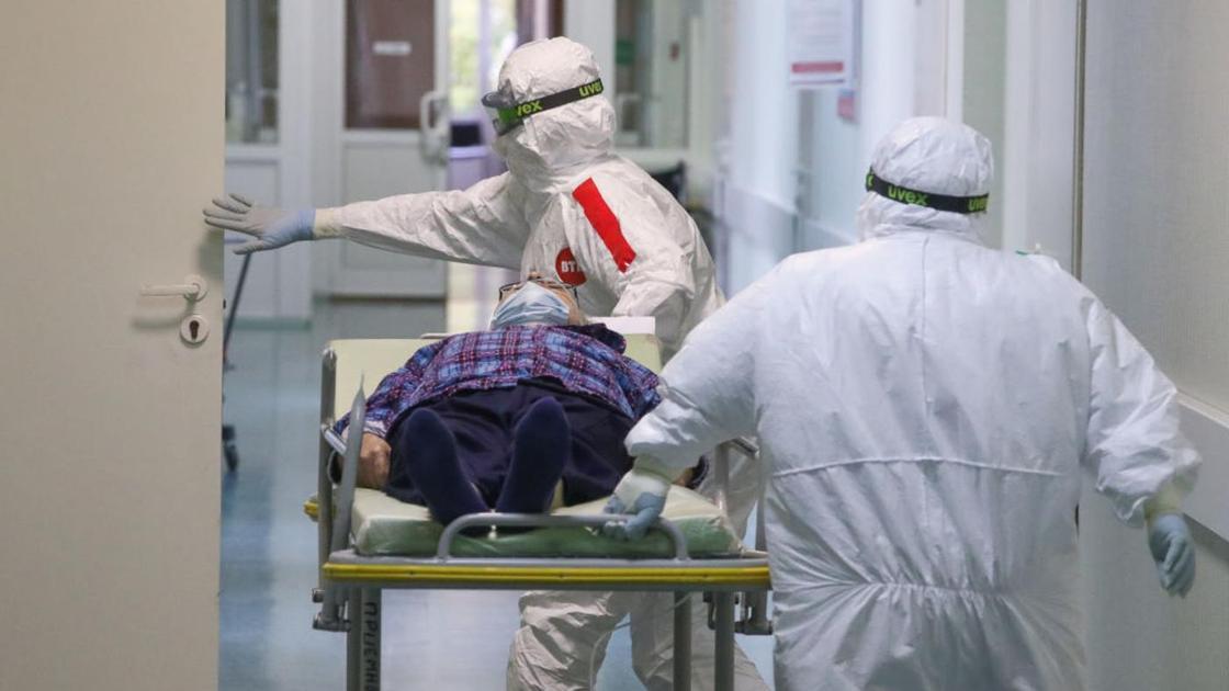 Врачи в защитных костюмах везут больного по коридору
