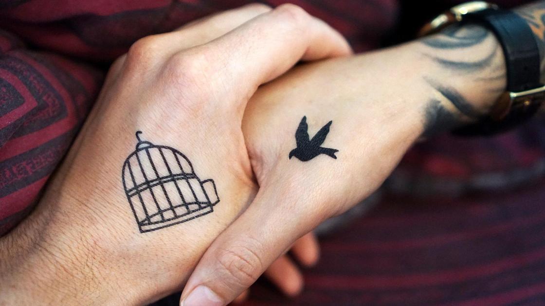 Руки с татуировкой клетки и птички