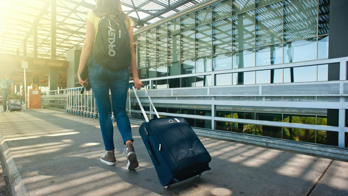 Девушка с рюкзаком и чемоданов идет в аэропорт