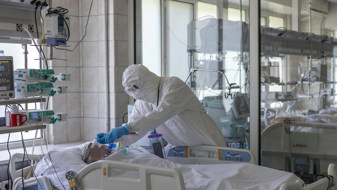 Врач подключает пациента к ИВЛ