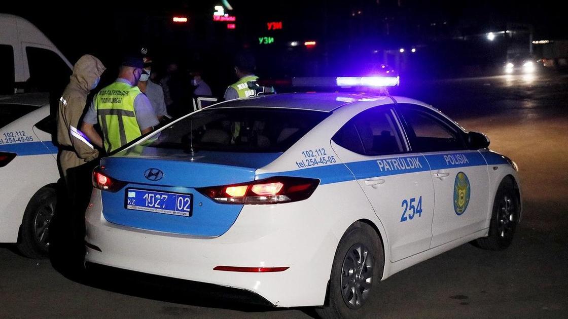 Полицейские стоят рядом со служебным авто с включенными мигалками