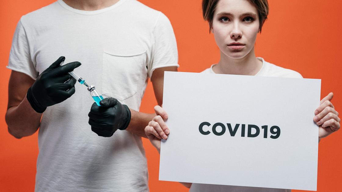Девушка с плакатом COVID-19 и парень с инъекцией