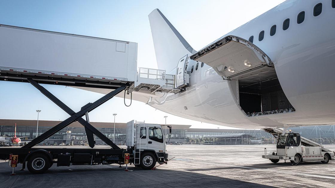 Самолет стоит на взлетно-посадочной полосе с открытым отсеком для багажа