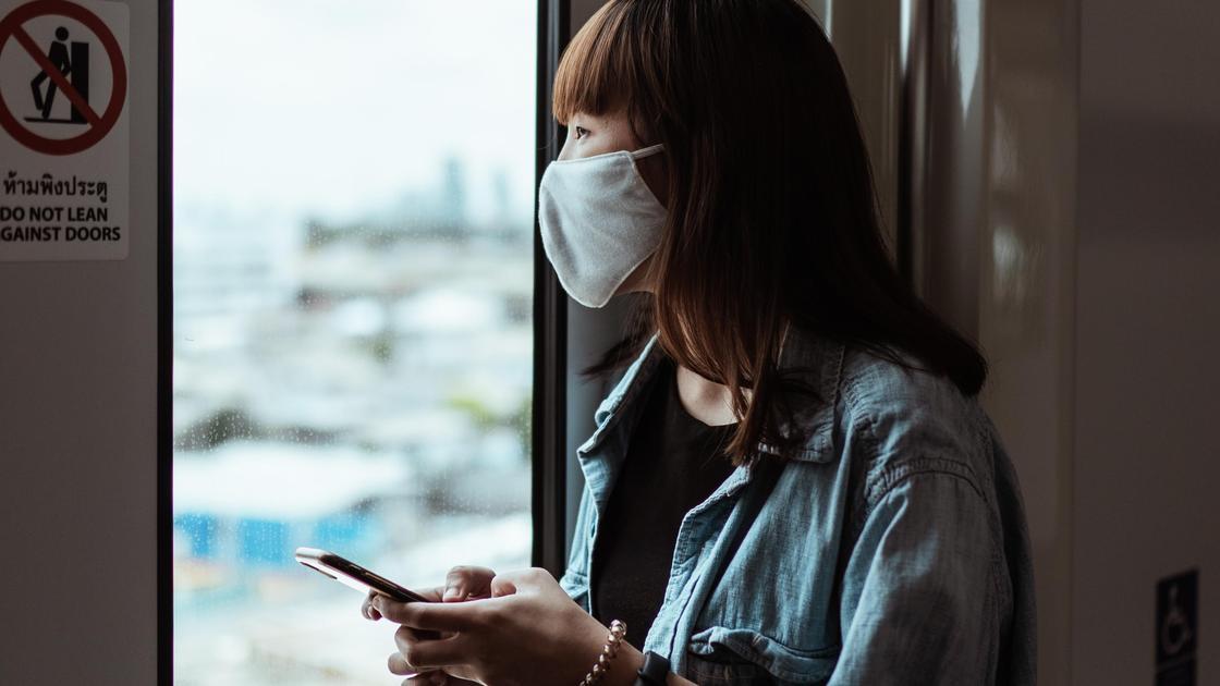 Девушка в маске смотрит в окно