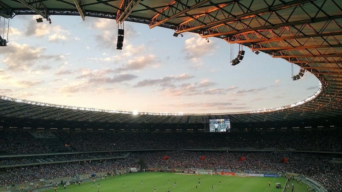 На большом стадионе зрители наблюдают за игрой в футбол