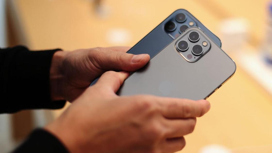 Мужчина держит в руках два iPhone 12 Pro