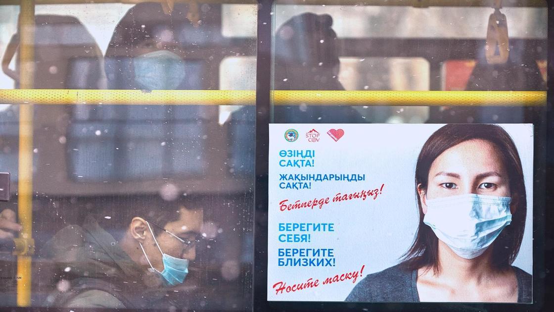 Плакат с девушкой в маске на окне автобуса