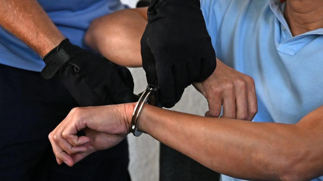 Мужчине на руки надевают наручники