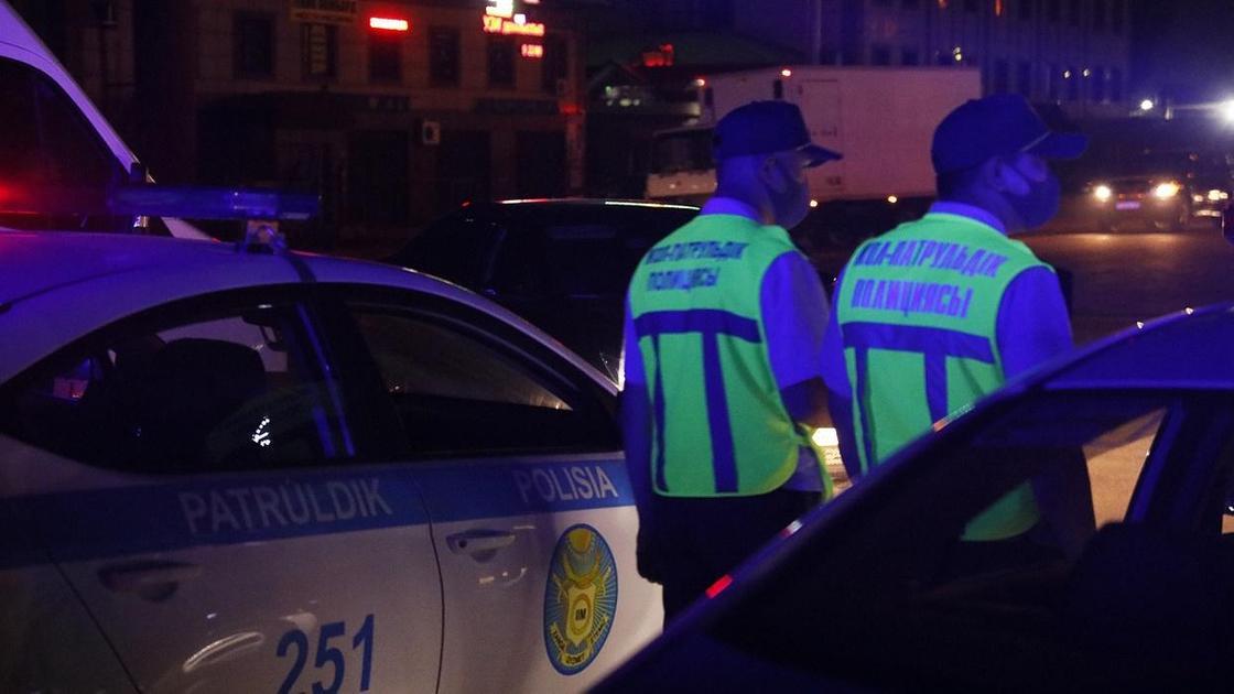 Патрульные полицейские стоят возле служебных авто