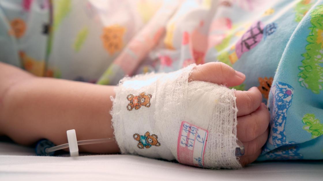 Рука ребенка под капельницей в бинте