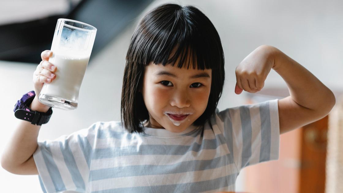 Ребенок держит стакан молока