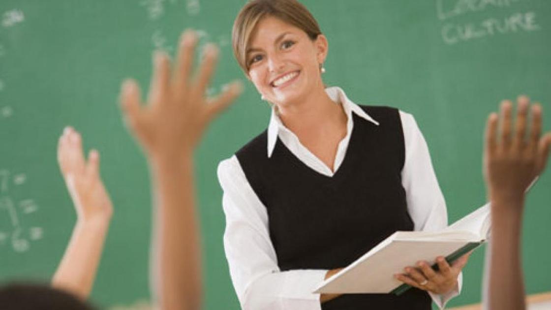 Учитель с книгой стоит возле доски