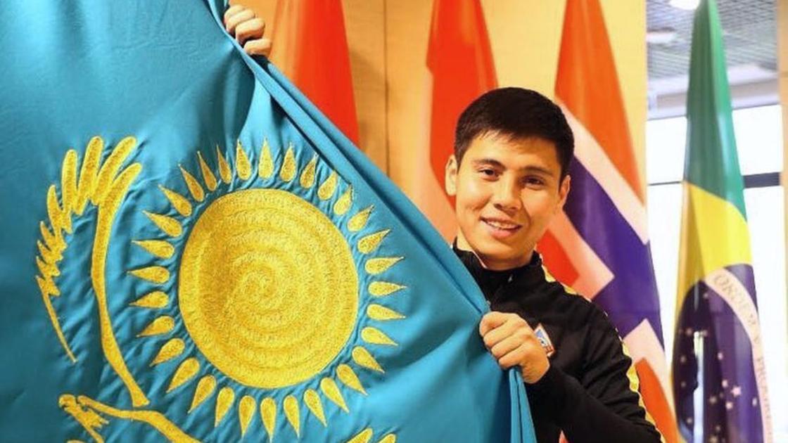 Бауыржан Исламхан держит в руках флаг Казахстана