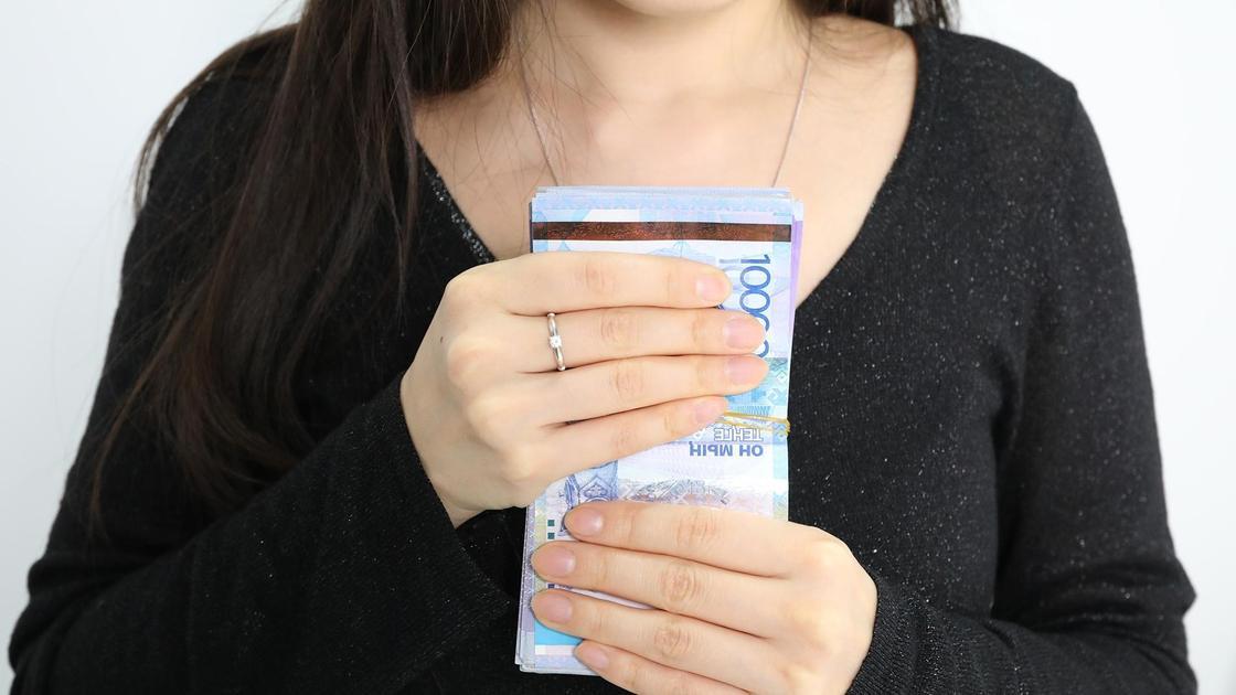Девушка держит в руках пачку денег
