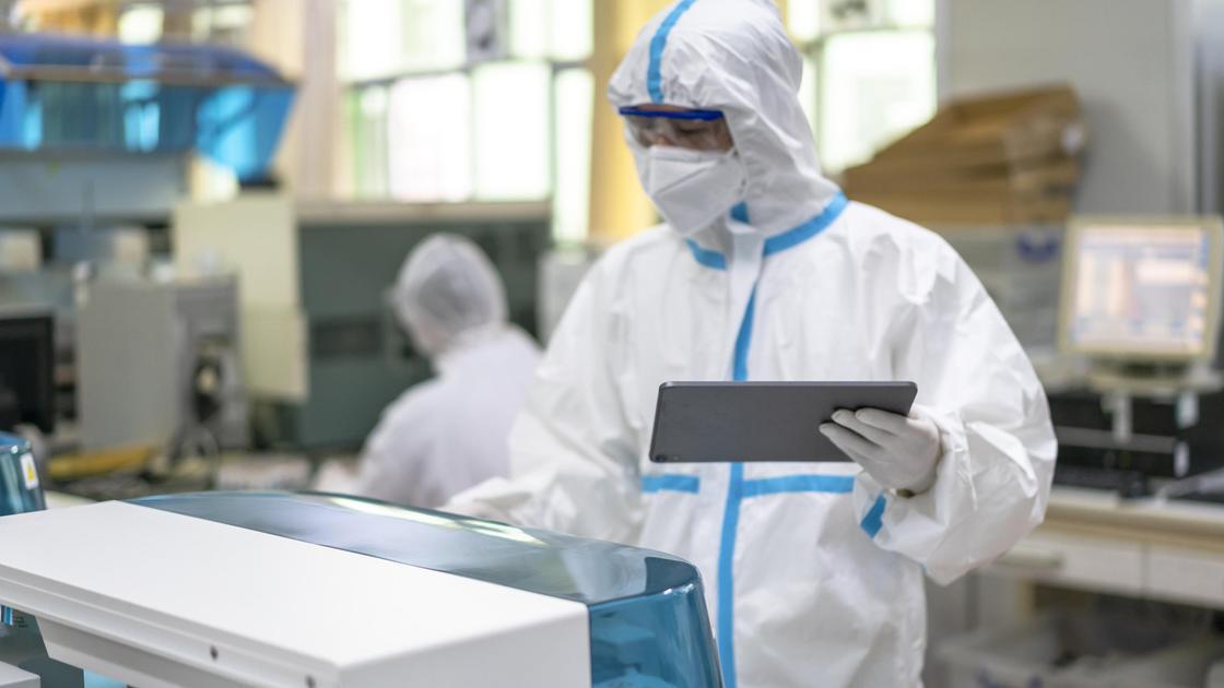 Медик в защитном костюме и с планшетом в руке стоит у медоборудования в больнице