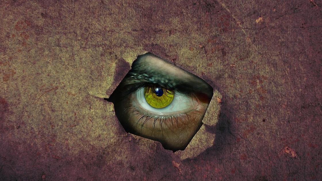 Кадр из фильма ужасов (глаз смотрит сквозь отверстие)