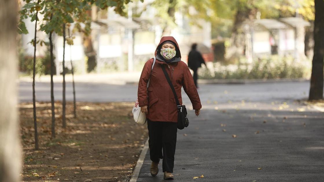 Женщина в куртке и маске идет по улице