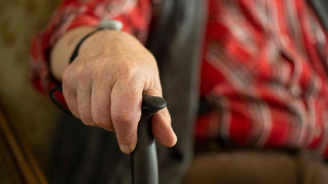 Пожилой человек держит в руке костыль