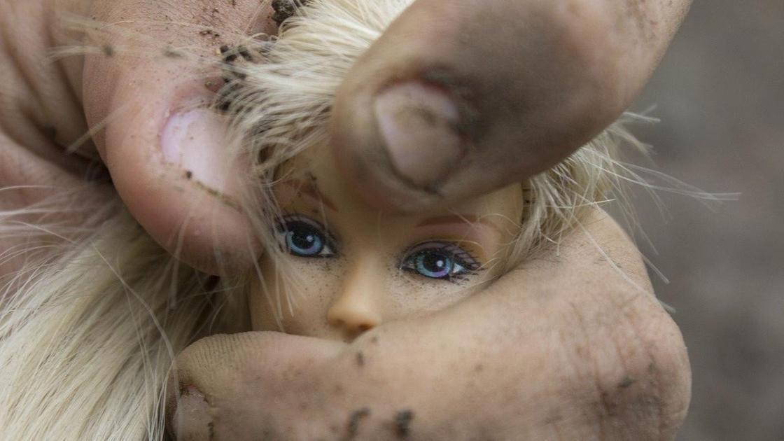 Рука сжимает куклу