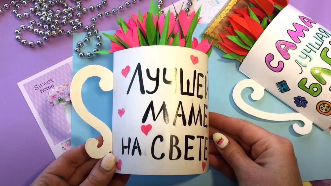 Женщина держит объемную открытку с 8 Марта