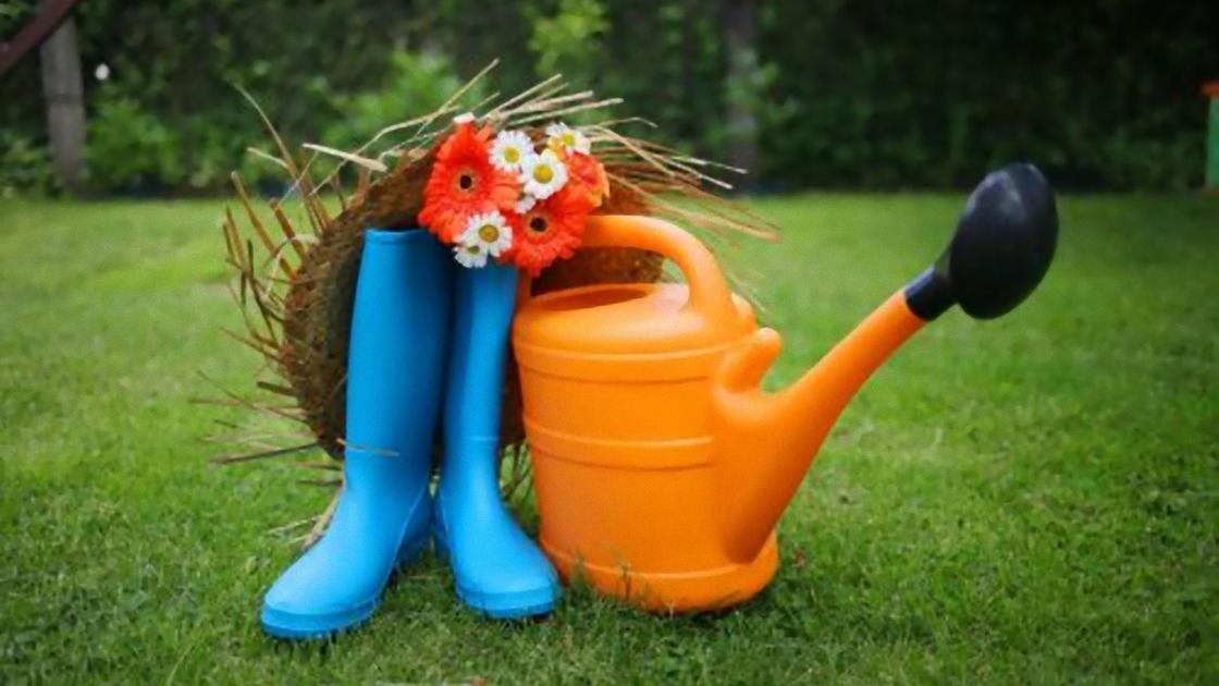 Сапоги, лейка, соломенная шляпа на газоне