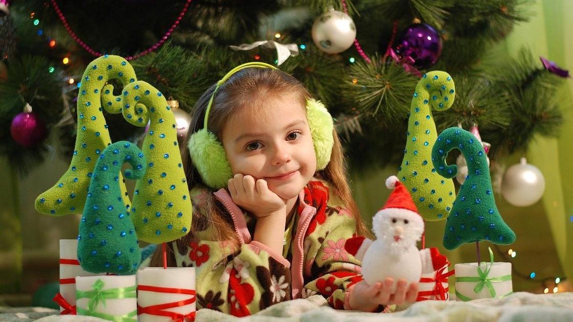 Девочка держит новогоднюю игрушку