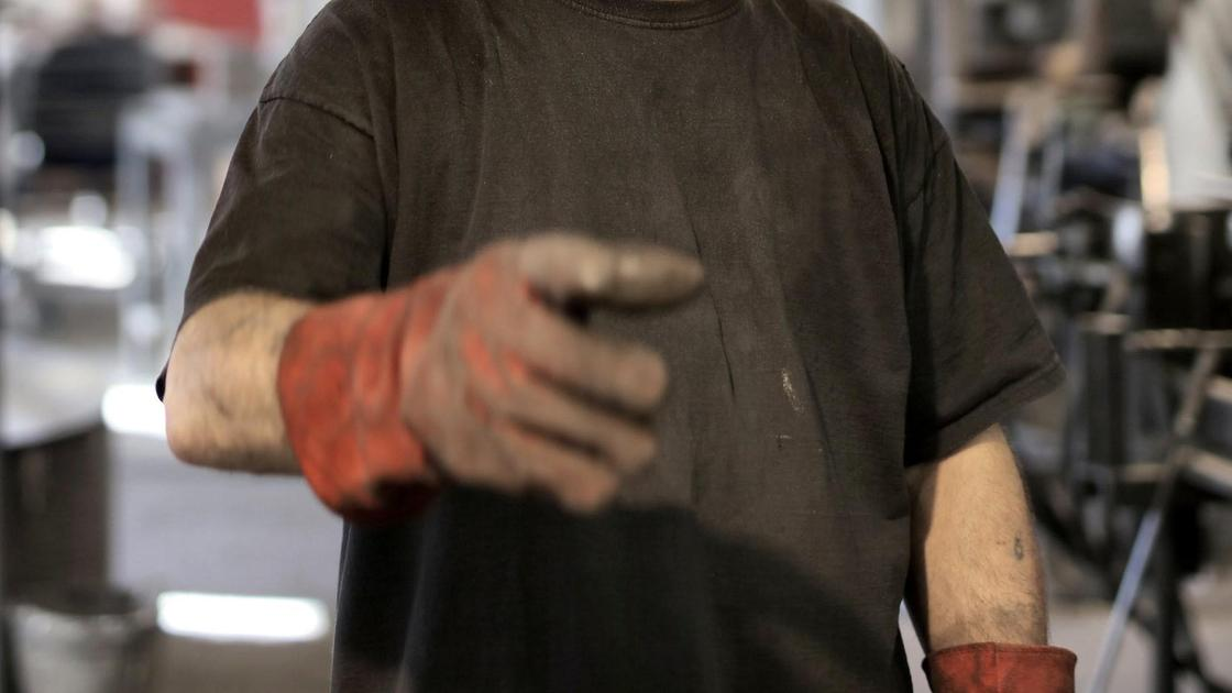 Мужчина на производстве в перчатках
