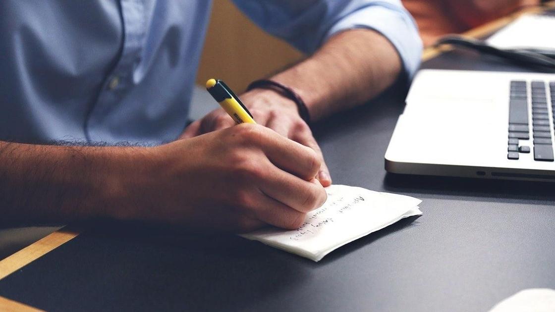 Парень пишет в блокноте