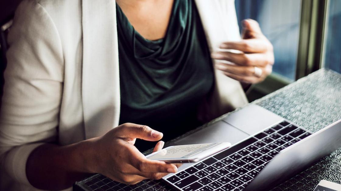 Девушка сидит с телефоном в руках перед ноутбуком