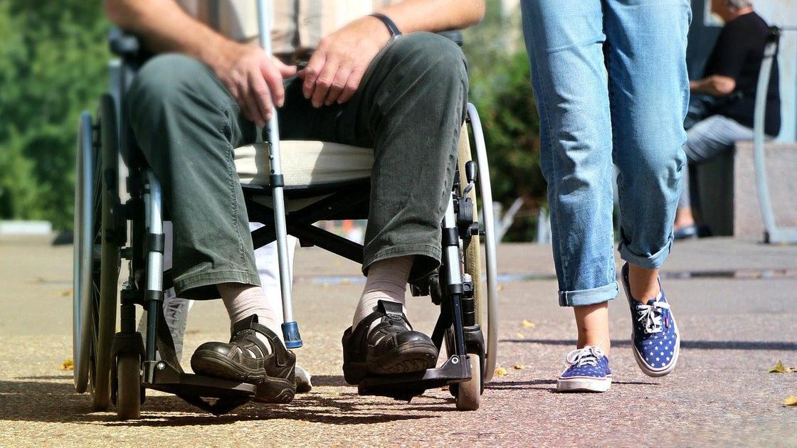 Мужчина с тростью сидит в инвалидной коляске