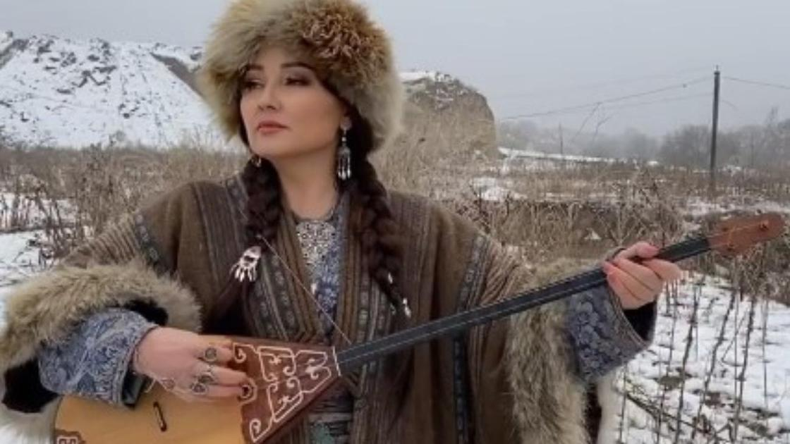 Жазира Байырбекова домбырамен ән салып тұр
