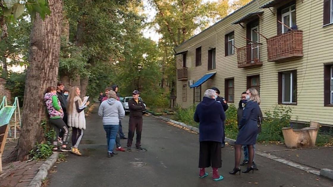 Люди стоят на улице перед домом в Усть-Каменогорске