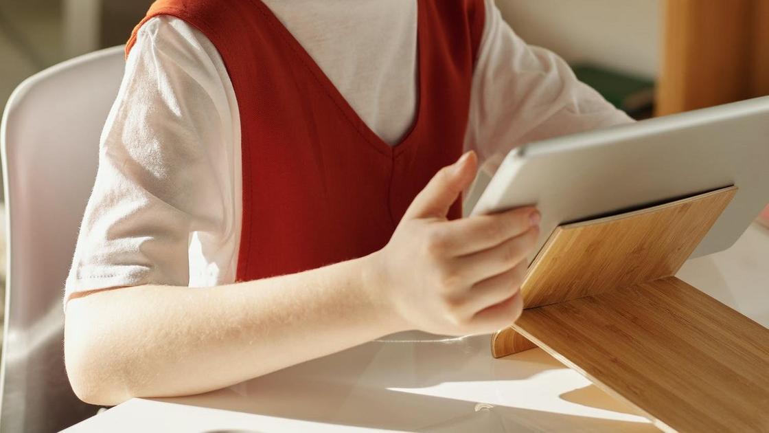Девочка сидит с планшетом в руках