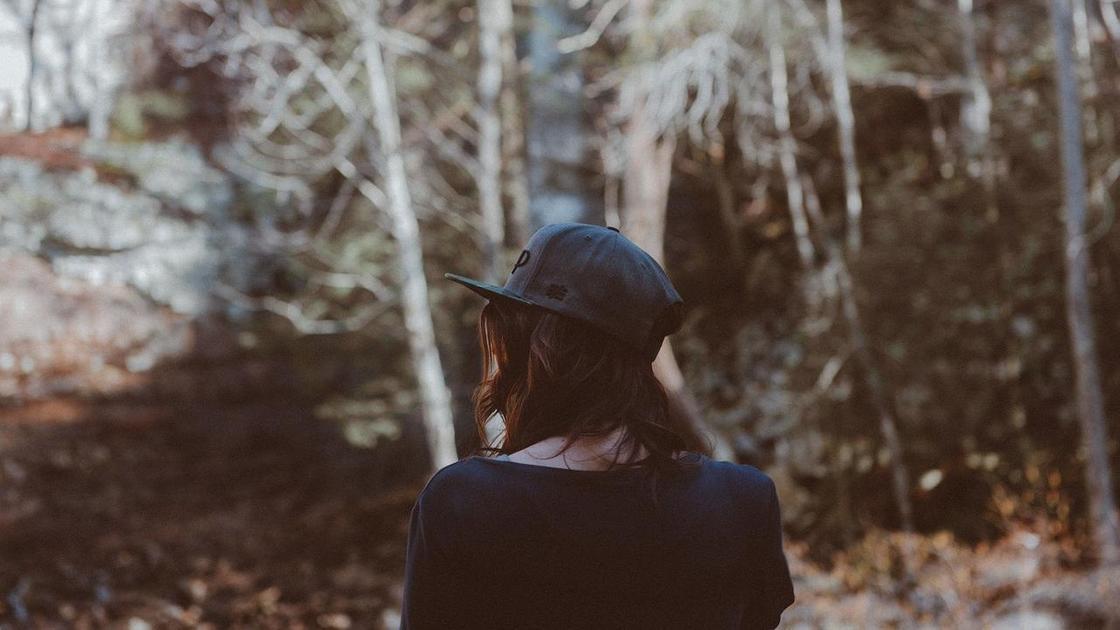 Девушка в кепке стоит спиной