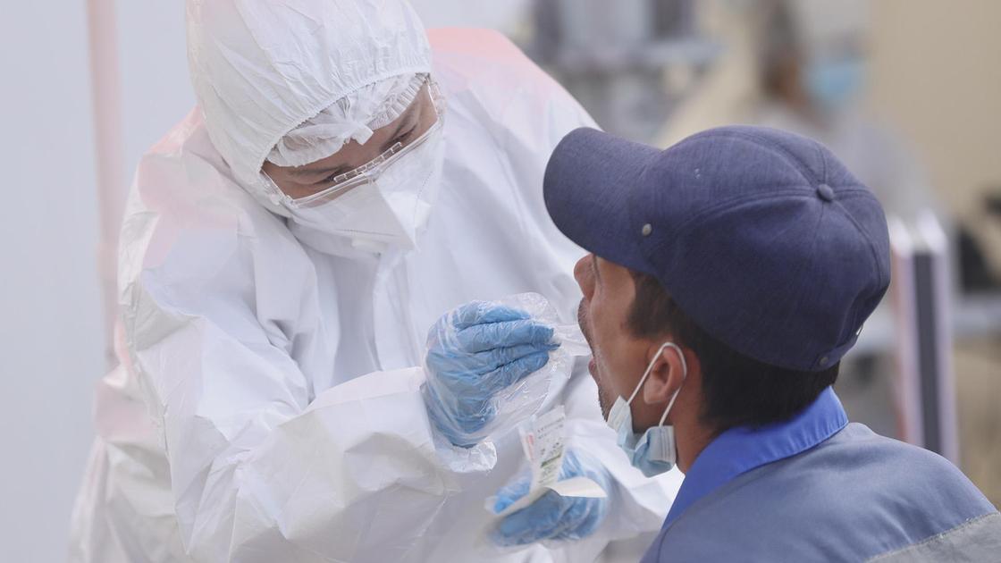 Врач в защитном костюме осматривает пациента