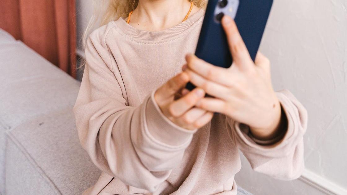 Девочка держит телефон в руках
