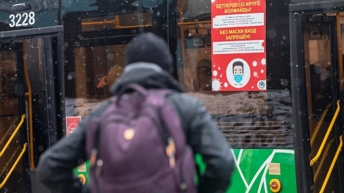 Мужчина с рюкзаком стоит возле автобуса