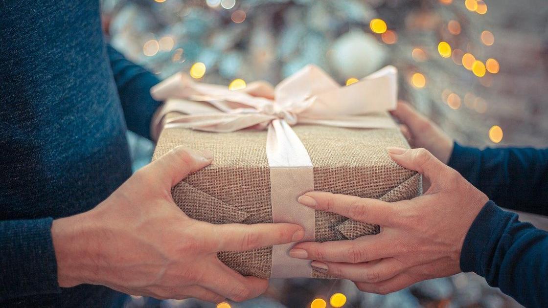 Девушка передает подарок мужчине