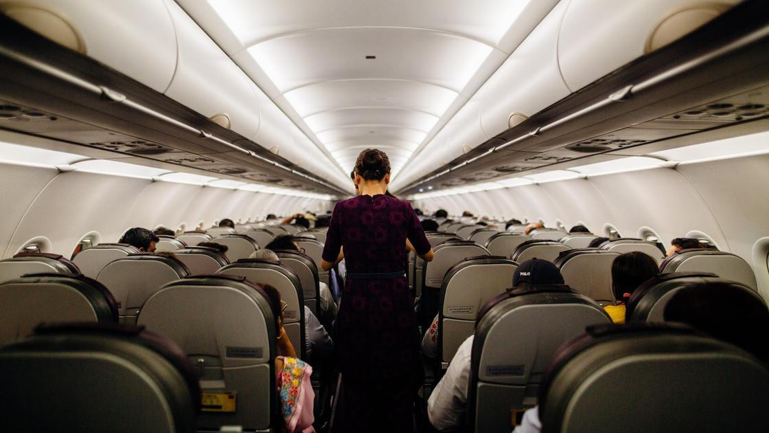Люди сидят и ходят на борту самолета
