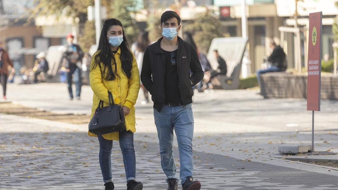Парень и девушка в масках гуляют по улице