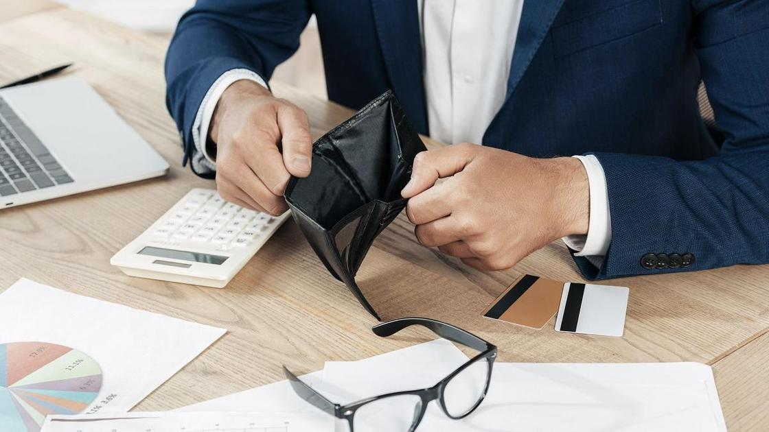 Мужчина держит пустой кошелек