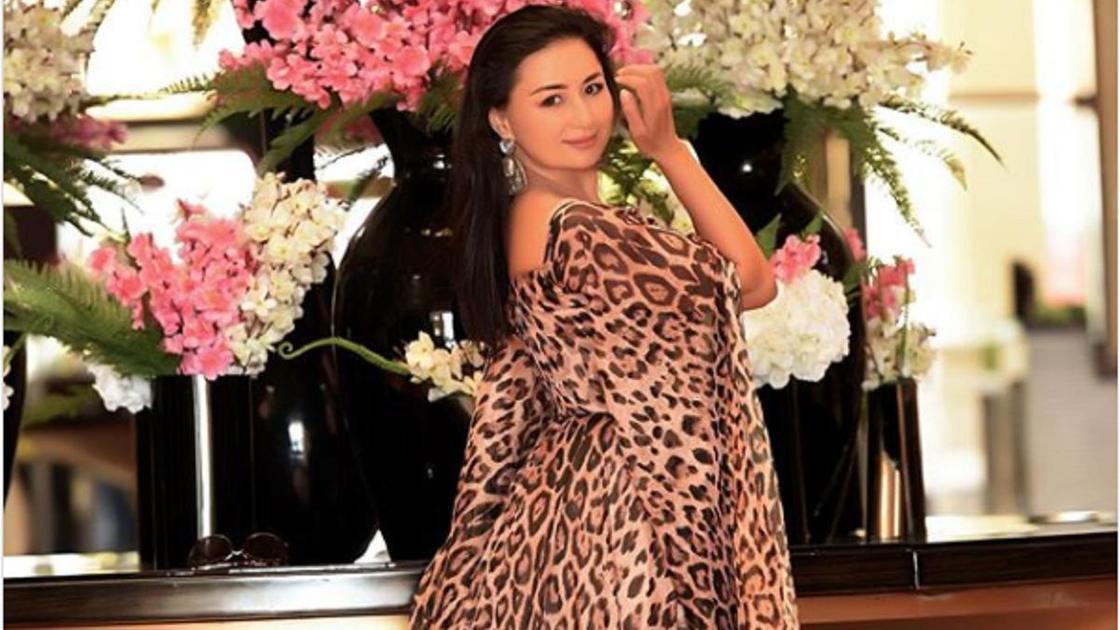 Мадина Садвакасова стоит на фоне цветов в платье с леопардовым принтом