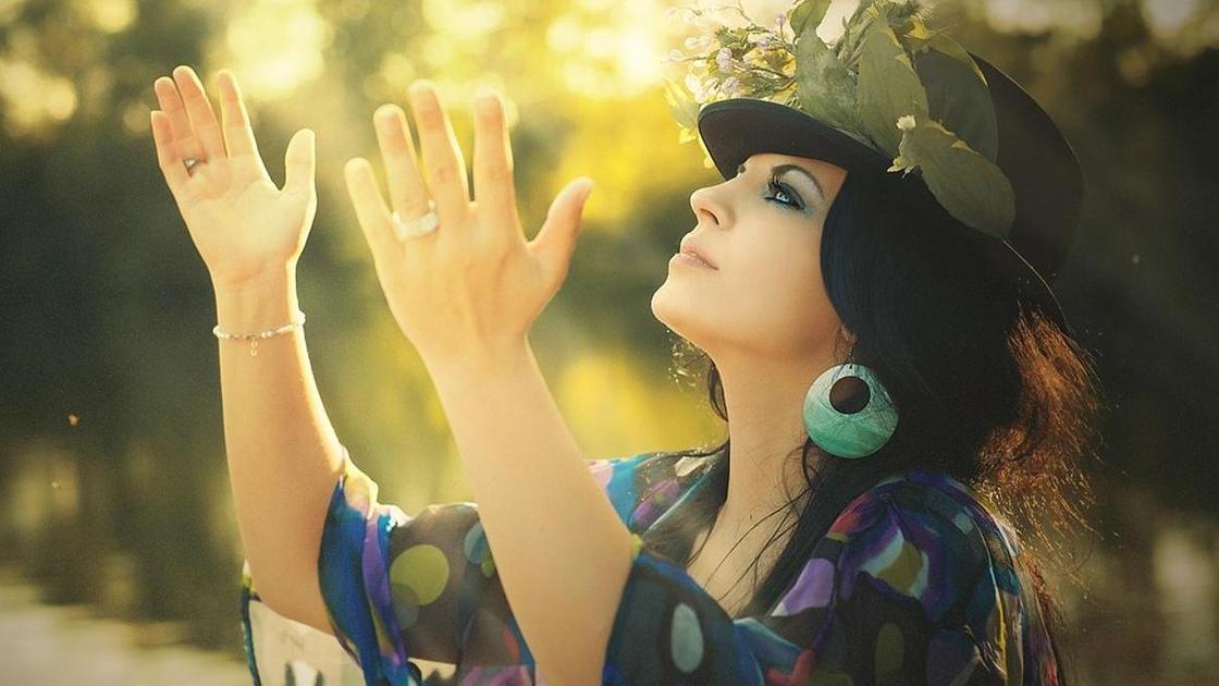 Женщина в шляпе подняла руки к небу
