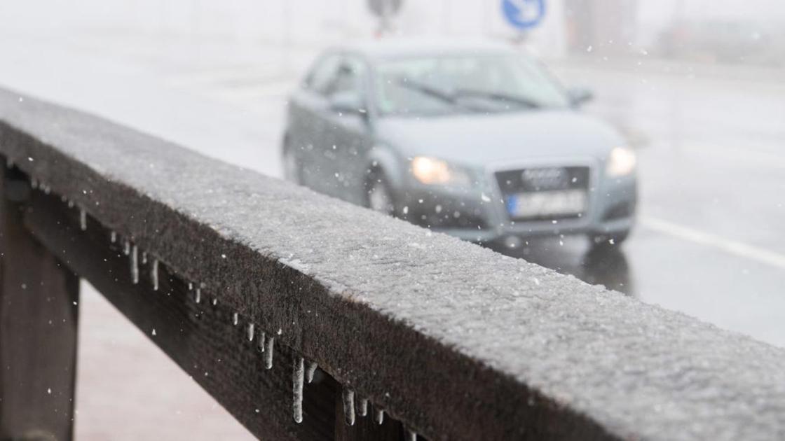 Машина едет по дороге в снежную погоду
