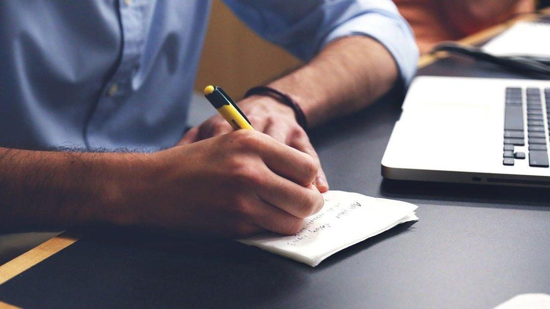 Человек пишет ручкой в блокноте на столе