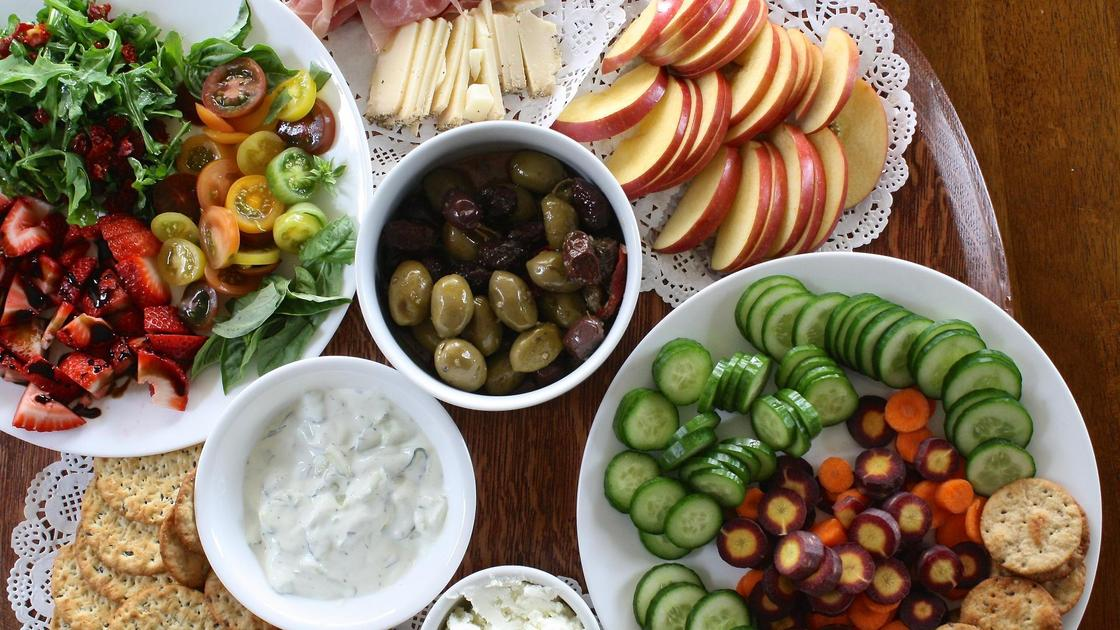 Тарелки с овощами и фруктами на столе