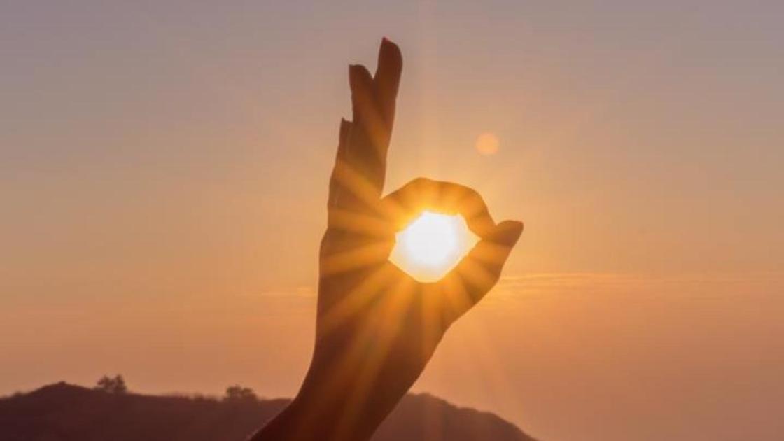 девушка держит солнце в кольце из пальцев