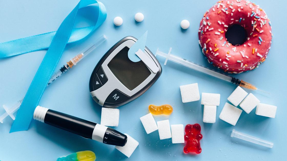 Пончик, сахар, глюкометр, шприц, лента на столе