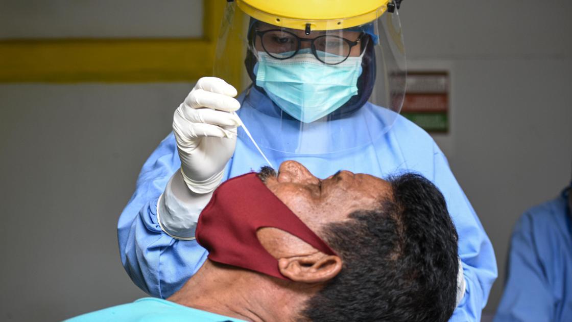 медик берет мазок на коронавирус у мужчины